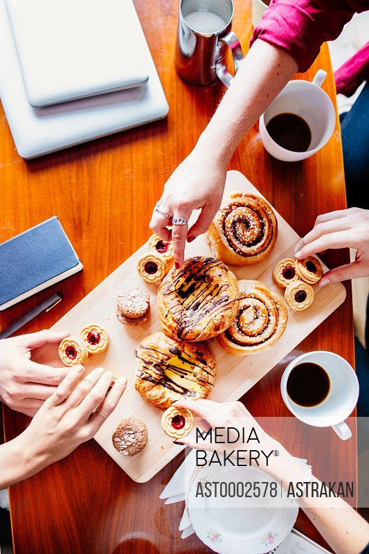 High angle view of business people having sweets at table