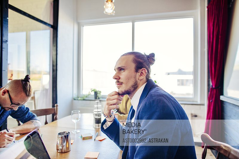 Thoughtful young businessman sitting at table in board room