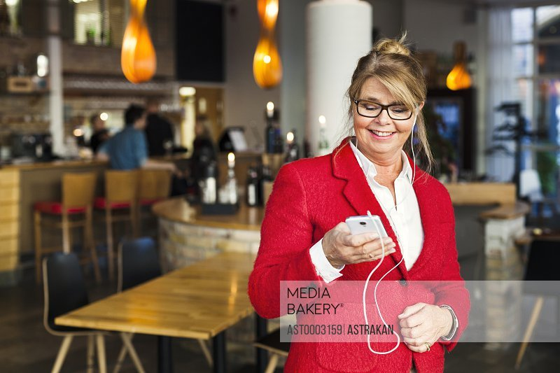 Happy businesswoman using smart phone while standing in restaurant