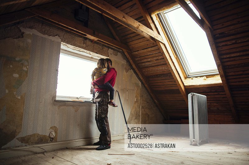 Full length of father and daughter looking through window in attic under construction
