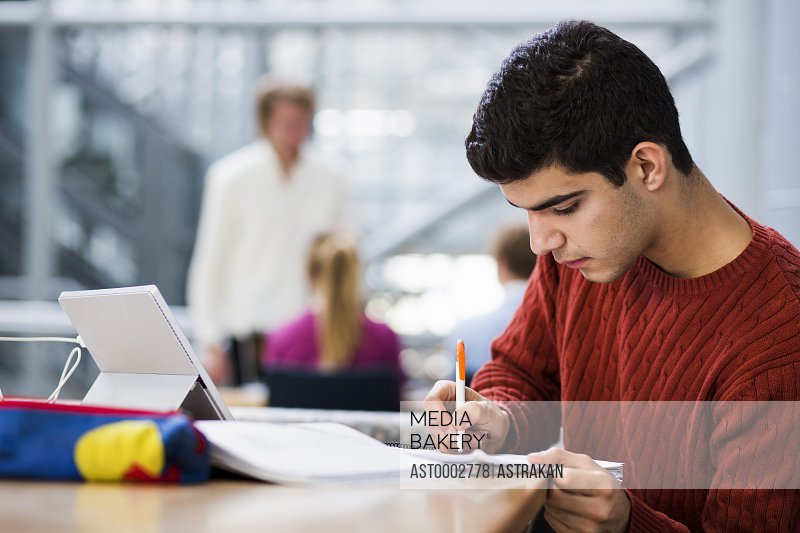 Young man writing in book at university