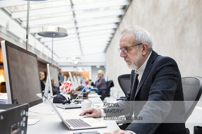 Side view of senior businessman using laptop at table in creative office
