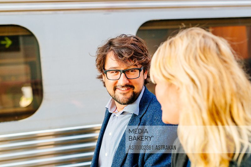 Happy businessman talking to female colleague at railroad station