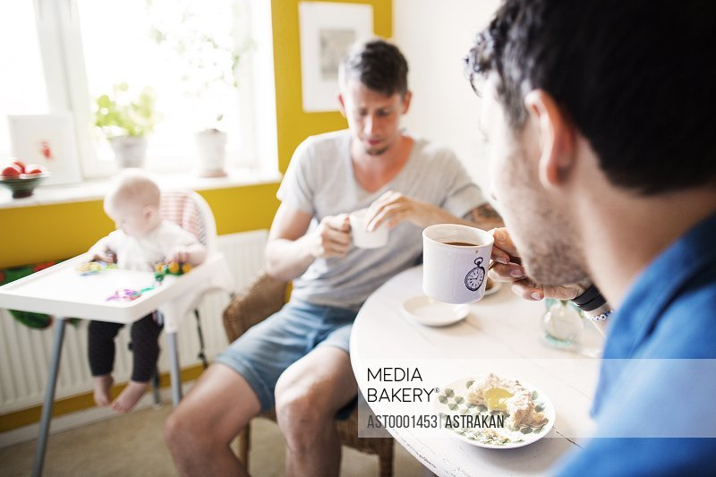 Gay men having breakfast while baby girl playing on high chair at home