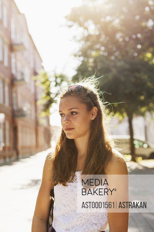Beautiful girl standing at street by building