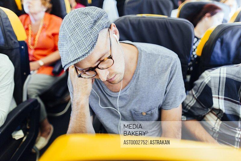 Businessman listening music while sleeping in airplane