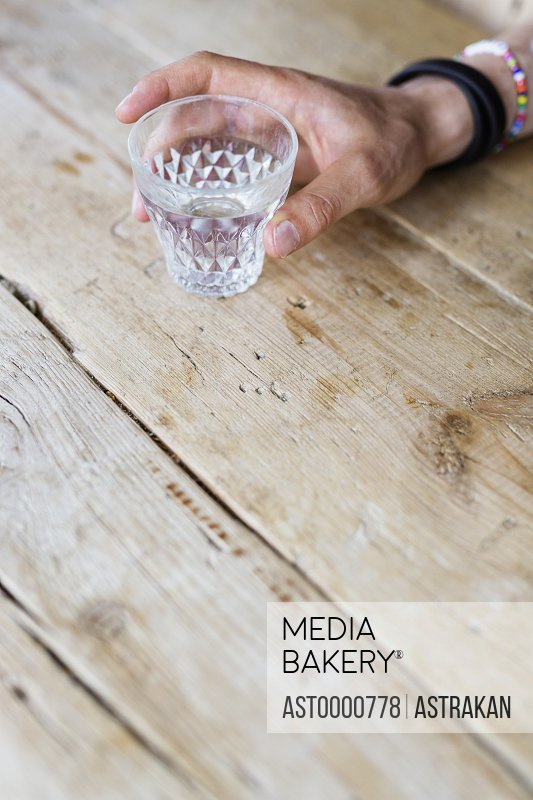 Cropped image of man holding drinking glass at cafe table