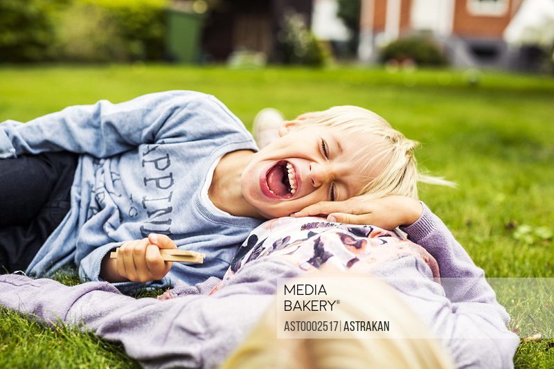 Cheerful boy lying on his sister's stomach in yard