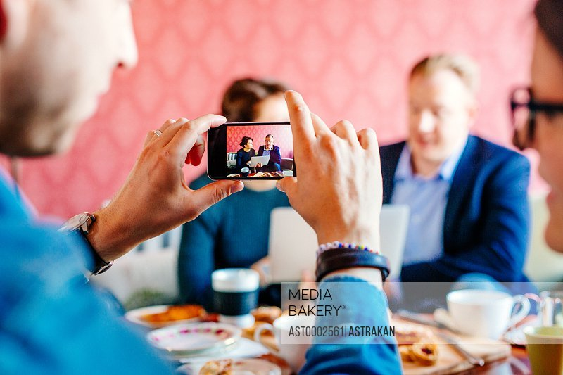 Cropped image of businessman photographing colleagues during meeting in office