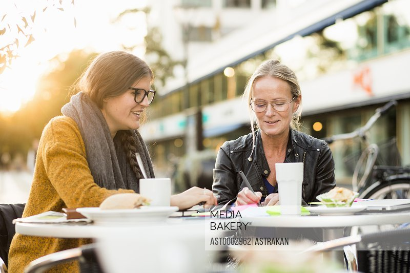 Happy colleagues discussing about project at sidewalk cafe