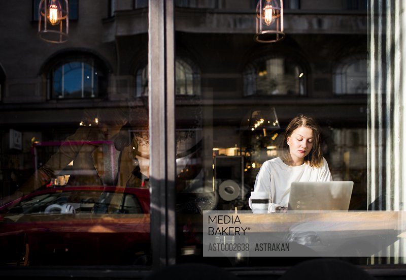 Woman using laptop in cafe seen through glass window