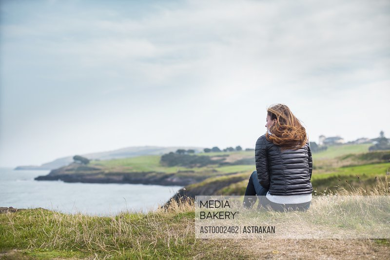 Rear view of woman looking away while sitting on hill against sky