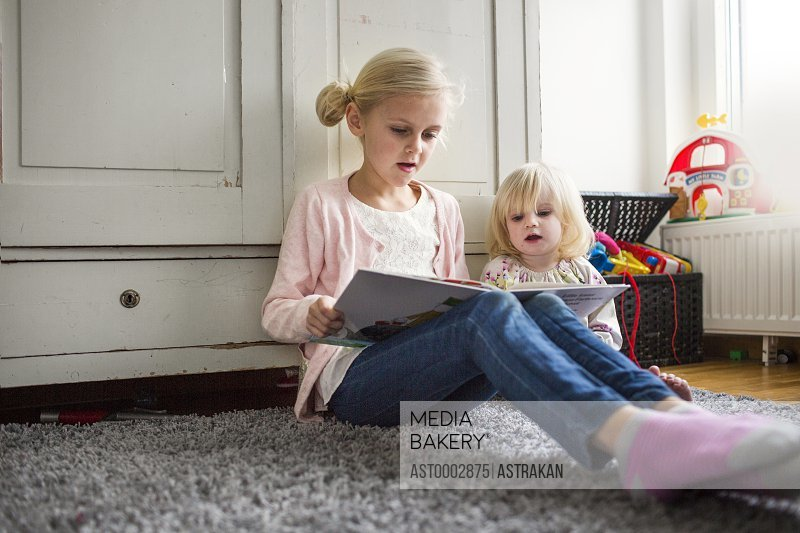 Sisters reading book while sitting on carpet at home