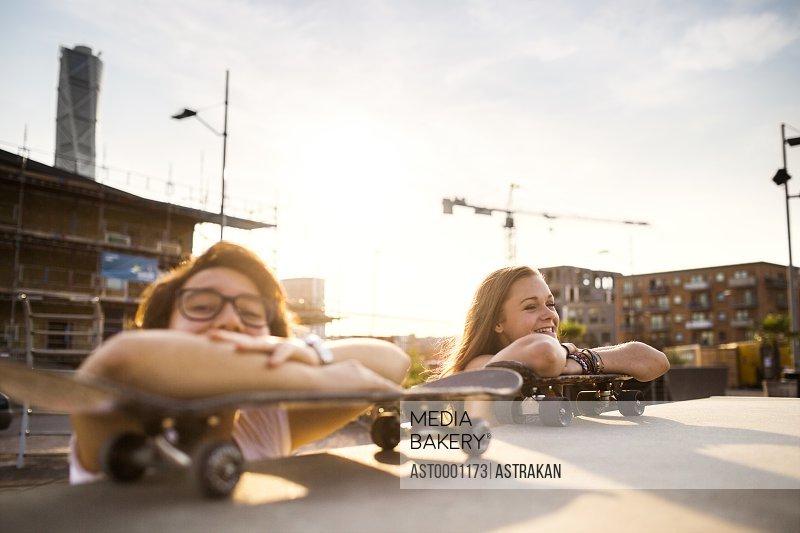 Happy teenage girls relaxing on skateboards at skate park