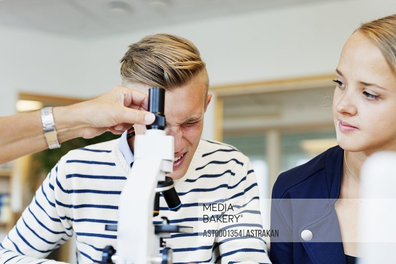 Cropped image of professor assisting student in using microscope in classroom