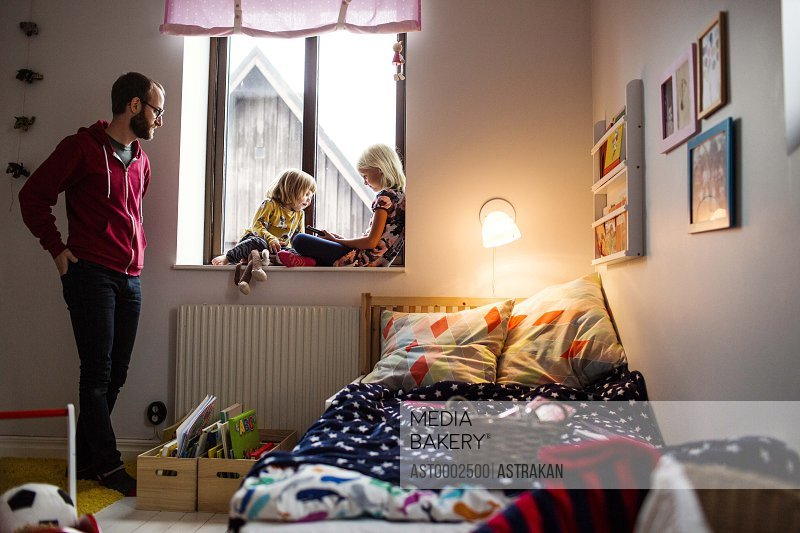 Mid adult man watching daughters using digital tablet on window sill