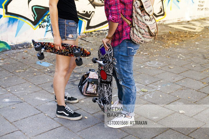 Low section of girls holding skateboards standing on street