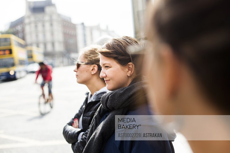 Smiling woman with friends standing on city street