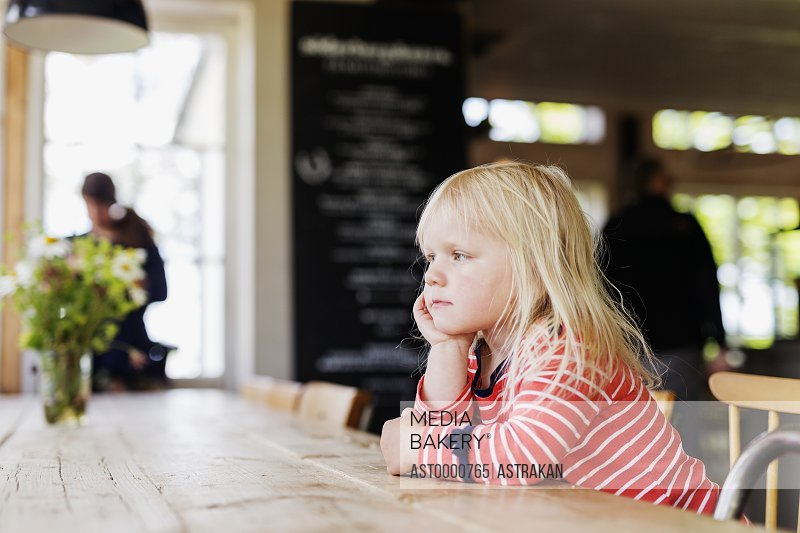 Side view of girl looking away while sitting at cafe table