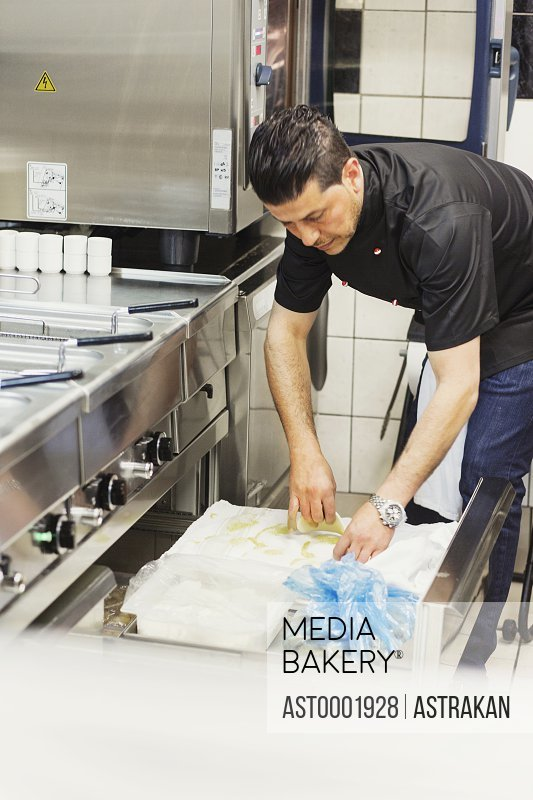 Male chef working in commercial kitchen at Lebanese restaurant