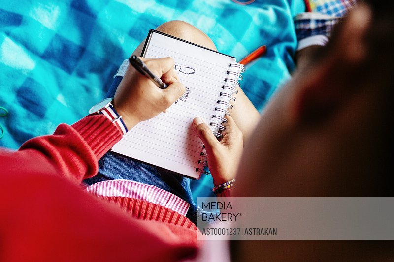 High angle view of university student writing in diary at park