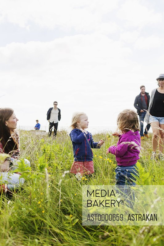 Family on grassy field against cloudy sky
