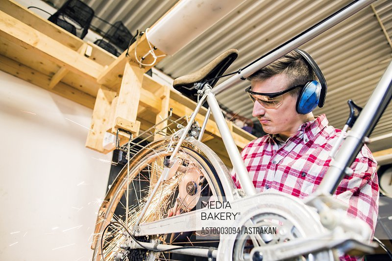 Mechanic using welding torch on bicycle in workshop