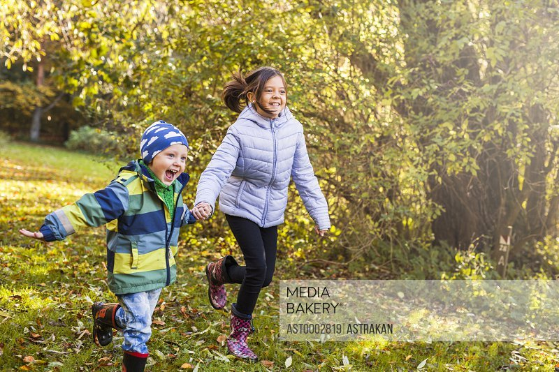 Playful brother and sisters holding hands while running in forest