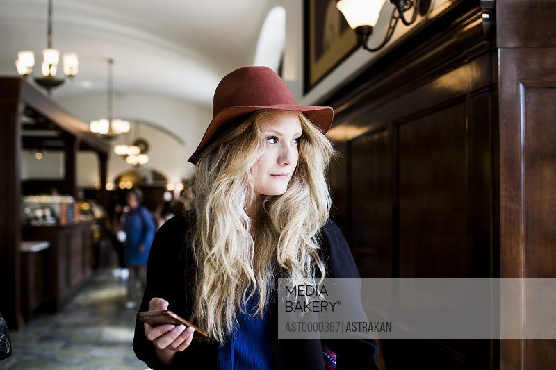Thoughtful freelancer holding smart phone while standing at cafe