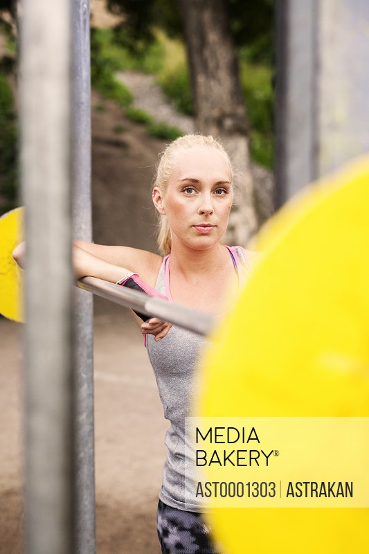 Portrait of young woman leaning on barbell at park