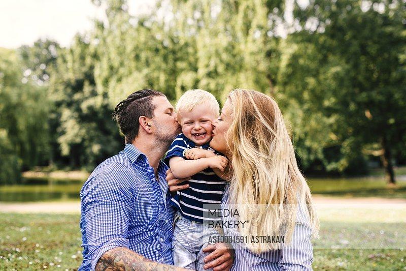Parents kissing happy son