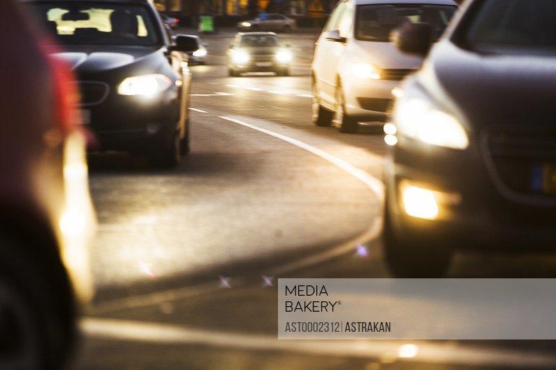 Illuminated headlights of cars on road
