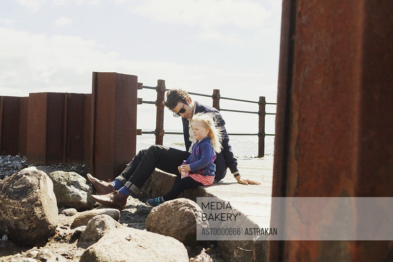Father and daughter sitting on pier against sky