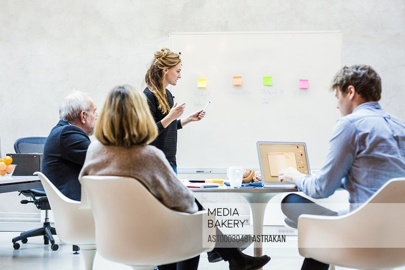 Mid adult businesswoman giving presentation to colleagues in board room