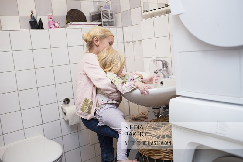 Sister helping girl in washing hand