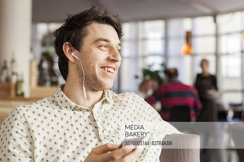 Happy businessman talking through earphones at restaurant