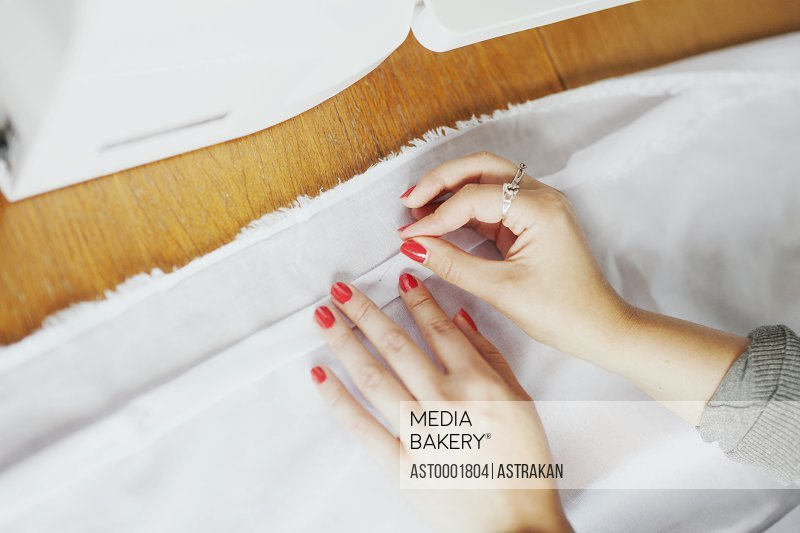 High angle view of designer pinning white fabric at table