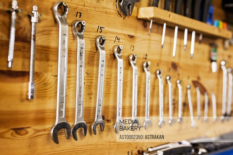 Various sizes of spanners hanging on wooden wall at workshop
