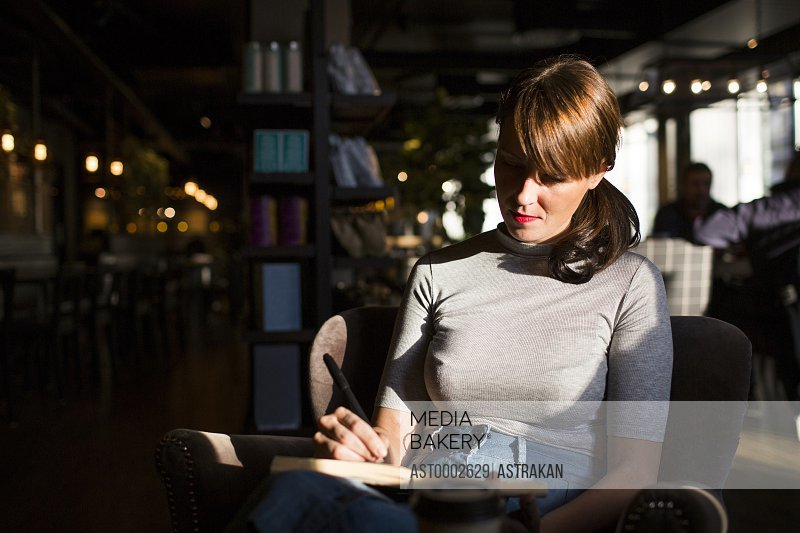 Mid adult woman writing in diary while sitting at cafe
