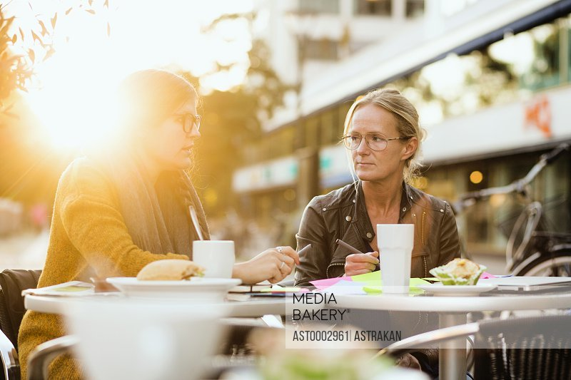 Businesswoman discussing with colleague about project on table at sidewalk cafe
