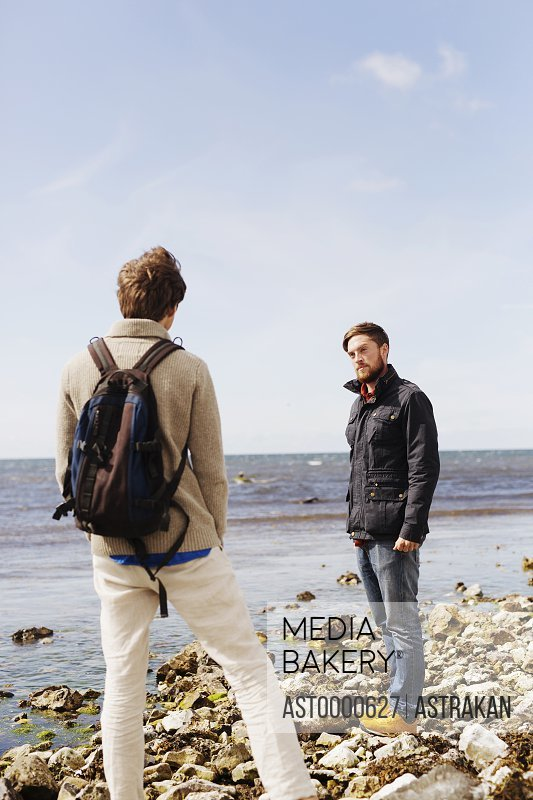 Friends standing at beach against sky