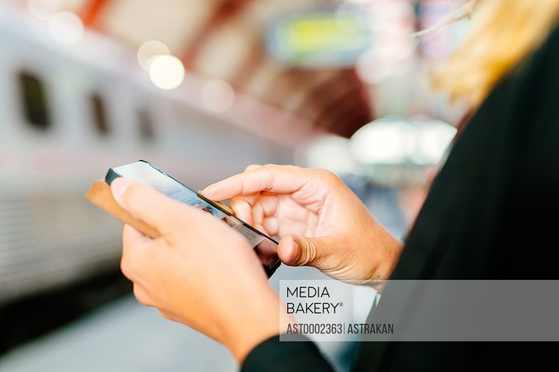 Cropped image of businesswoman using smart phone at railroad station