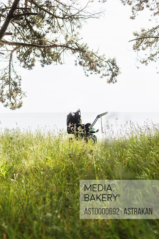 Baby carriage on grassy field against sky