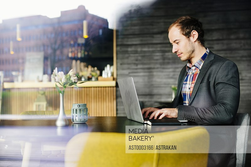 Young businessman using laptop while sitting at restaurant