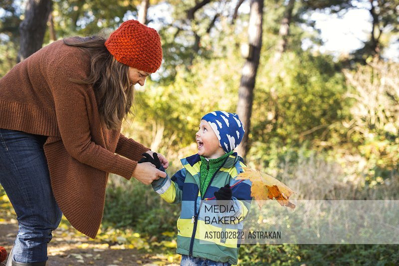 Mature mother with playful boy holding leaf in forest during autumn