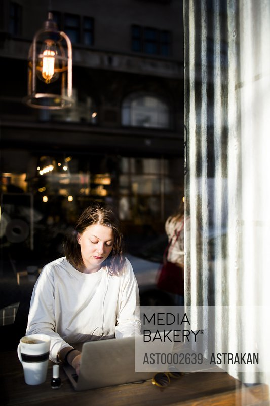 Woman using laptop seen through cafe window