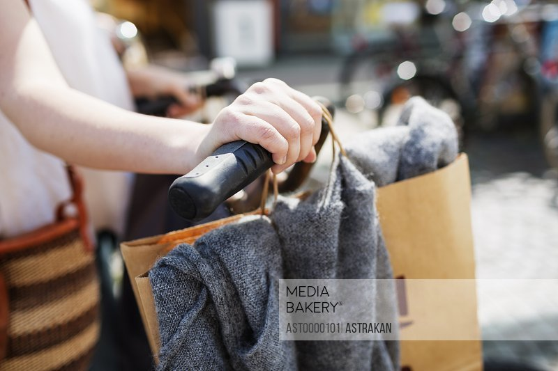 Woman holding bicycle handlebar with shopping bags on sidewalk