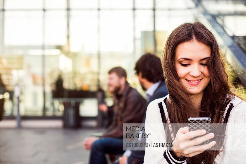 Smiling businesswoman using smart phone outside railroad station