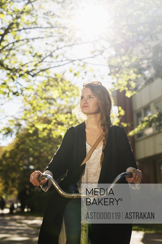 Beautiful young woman riding bicycle on city street