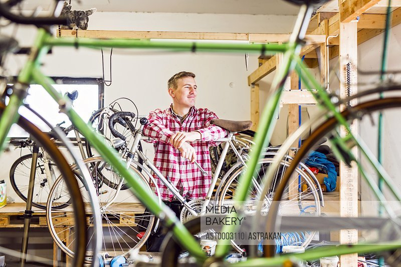 Thoughtful mechanic leaning on bicycle at workshop